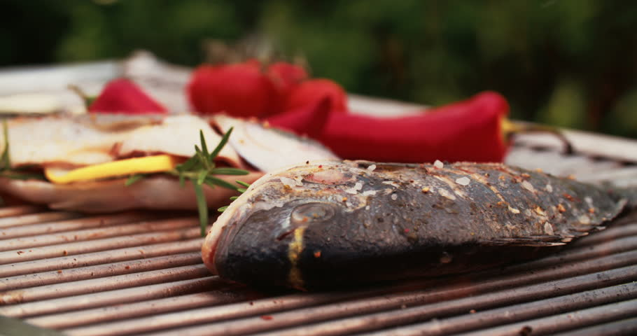 Two fresh whole fish stuffed with lemon and rosemary being grilled on a hot barbecue outdoors, flames in Slow Motion