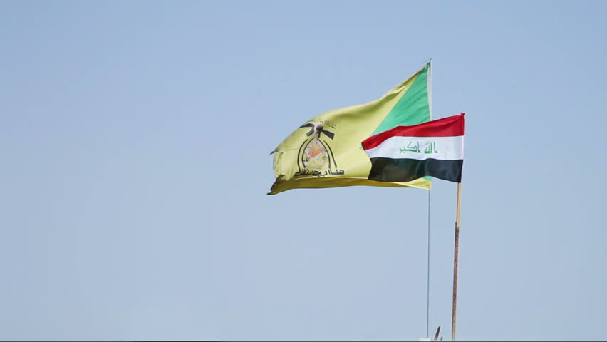 Iraqi and Hezbollah Battalions' flags wave in the wind. Hezbollah Battalions is an Iraqi Shia paramilitary group active in the Iraqi insurgency and Syrian Civil War