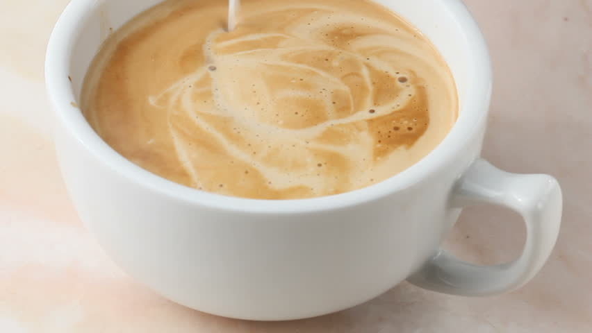 Frothy milk pouring into cappuccino