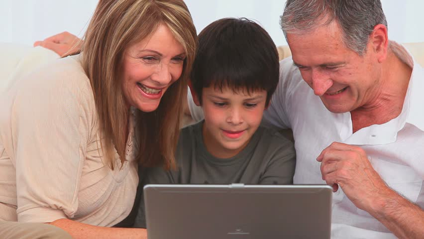 Grandparents and their grandson playing a game on a laptop - HD stock video clip