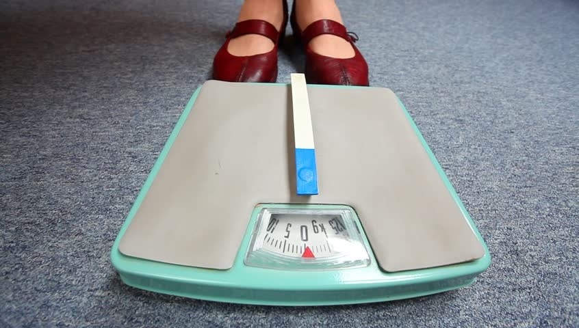 Overweight woman on a scale  - HD stock video clip