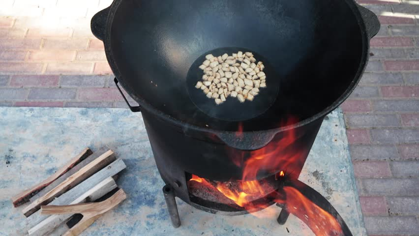 Uzbek national dish pilaf in a large cast-iron cauldron on the fire, the cooking process, fried pieces of fat tail, basis ??constituting food rice, lamb, carrot, mutton fat, sesame oil, onion, garlic - HD stock video clip