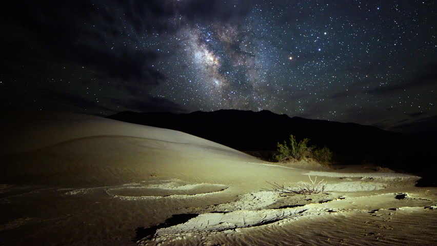 Astrophotography time lapse footage with pan right motion of Milky Way galaxy over desert sand dunes in Death Valley National Park, California