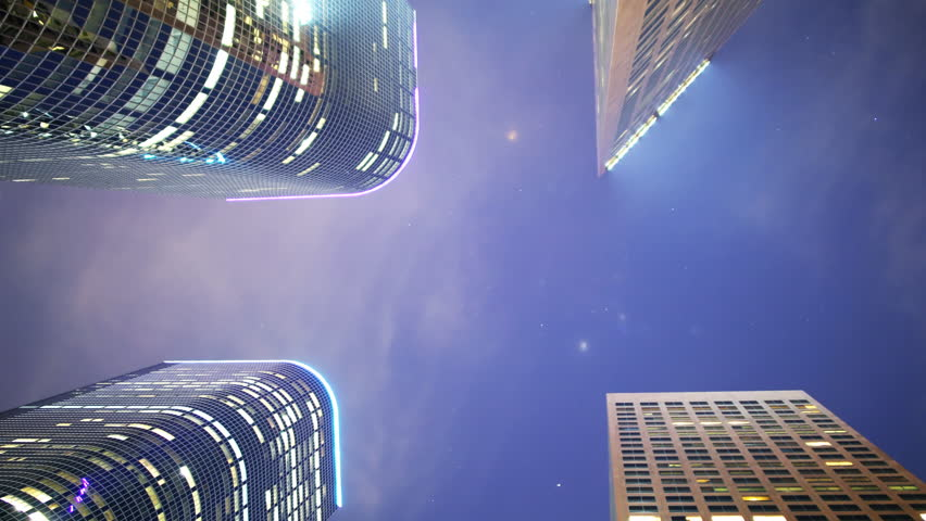 Time lapse footage with zoom out motion of low angle shot of skyscrapers with stars & clouds at night in downtown Los Angeles, California