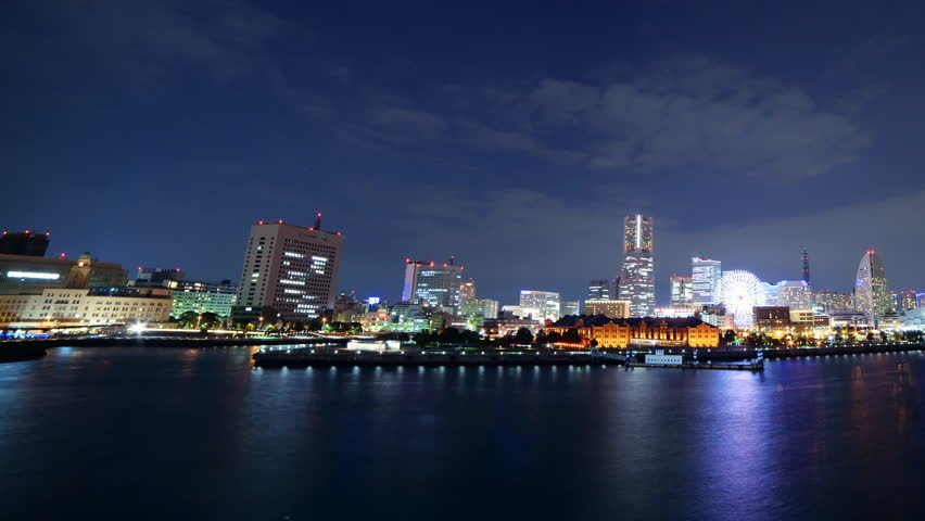 Time lapse footage with pan right motion of metropolitan city skyline over the bay at night in Yokohama, Japan