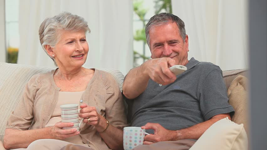 Mature couple watching tv in the living room - HD stock footage clip