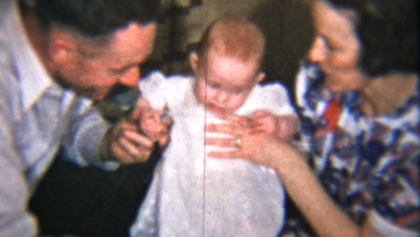 A proud mom and dad spend time with their beautiful red headed baby girl. from 8mm reels