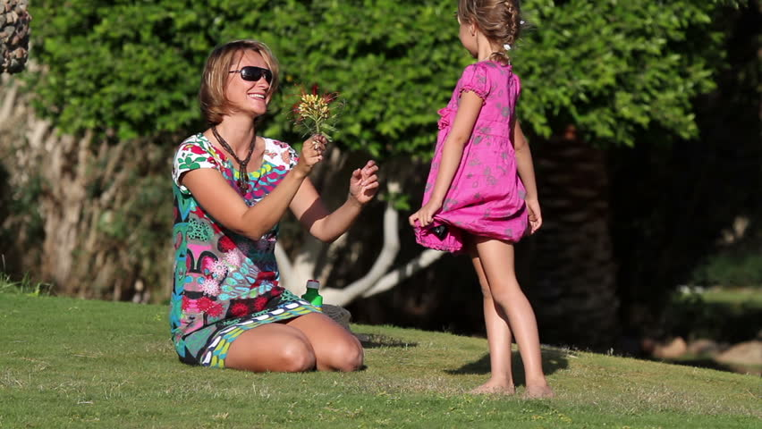 little girl hugging her mother on the lawn - HD stock video clip