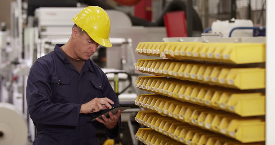 Male warehouse employee checking stock level on his digital tablet