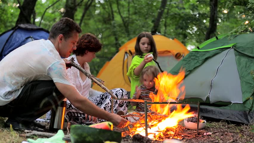 Man, woman, girl and boy sitting by the fire in the evening in a mountain forest. Family roasts marshmallows and fun laughing kids happy.