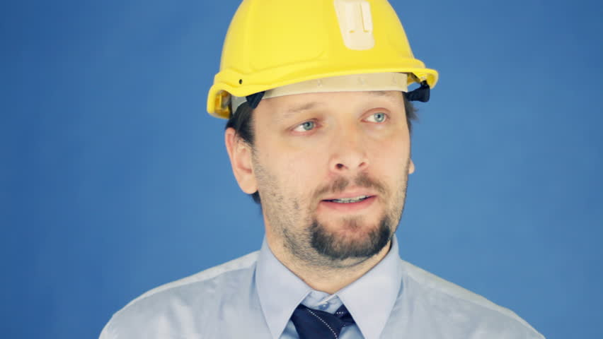 Successful engineer in yellow helmet showing ok sign, on blue background - HD stock video clip