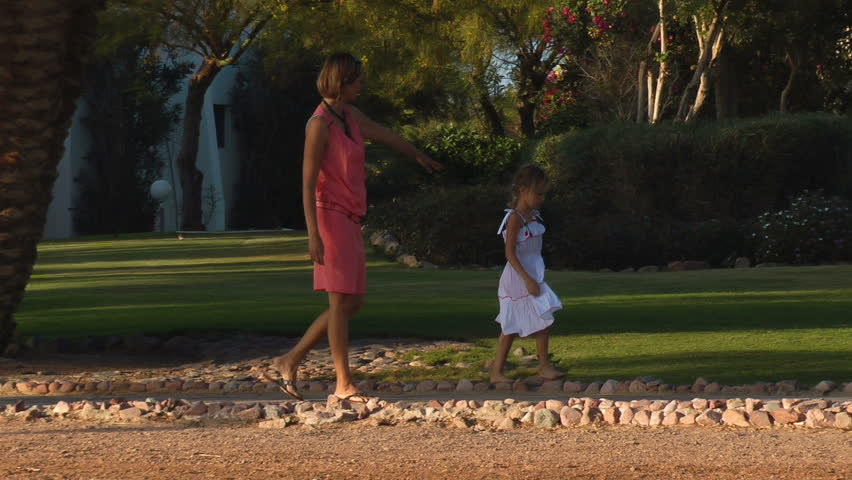 girl  and her mother walking on the sidewalk at sunset  - HD stock video clip