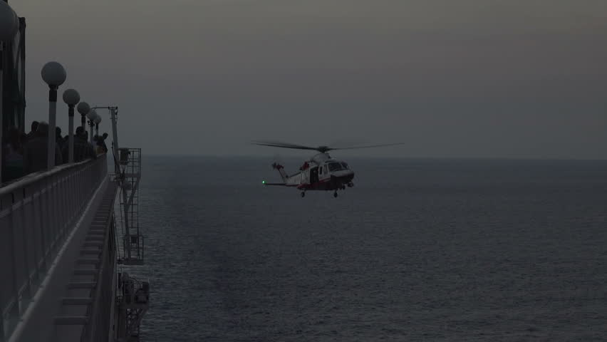 MEDITERRANEAN - SEPT 2014: Italian Coast Guard rescue evacuation helicopter cruise ship 4K. Emergency boat and rescue helicopter. Patient air lifted moving cruise ship, sunset partial darkness.