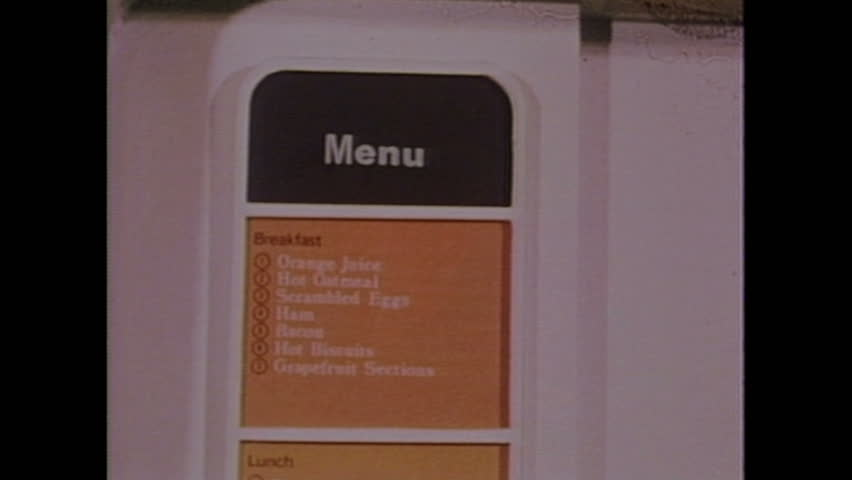 UNITED STATES 1970s: Panning shot of menu / Astronaut trains in weightless plane / Astronaut puts feet on equipment.