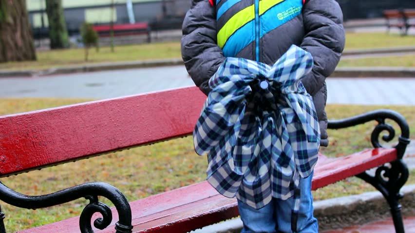 Little kid standing in park near bench on cold rainy day. Child opening umbrella. Rainy weather and schoolboy.