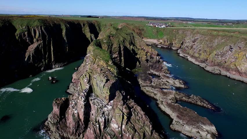 Aerial shot of sea cliffs off the coast of Scotland near Aberdeen - HD stock footage clip