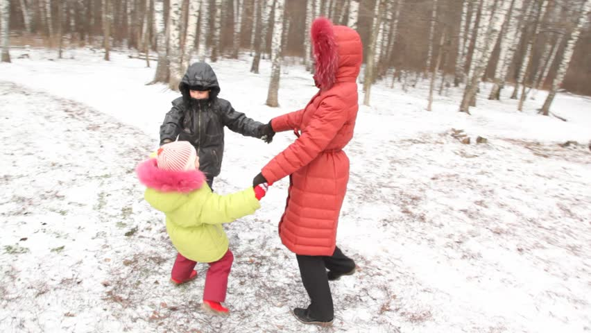 Happy mother with two children (boy and girl) in winter wood. - HD stock video clip