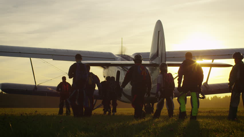 Group of Skydivers Moving Towards Airplane in Sunset Light. Shot on RED Cinema Camera in 4K (UHD).
