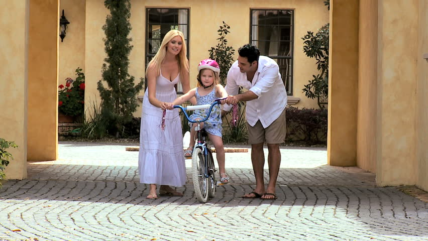 Cute little caucasian girl being encouraged by her multi-ethnic parents as she practices riding her bicycle - HD stock video clip