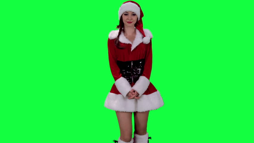 Sexy Santa's helper demonstrates an object chroma key (green screen). Sexy Santa girl holding the imaginary objects in hands isolated on green