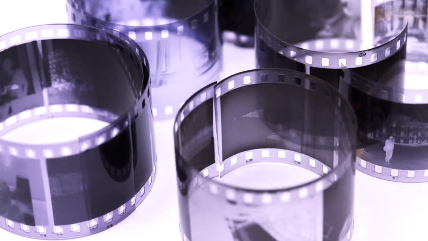 rolls of black and white negative film revolve on light surface, closeup - HD stock video clip