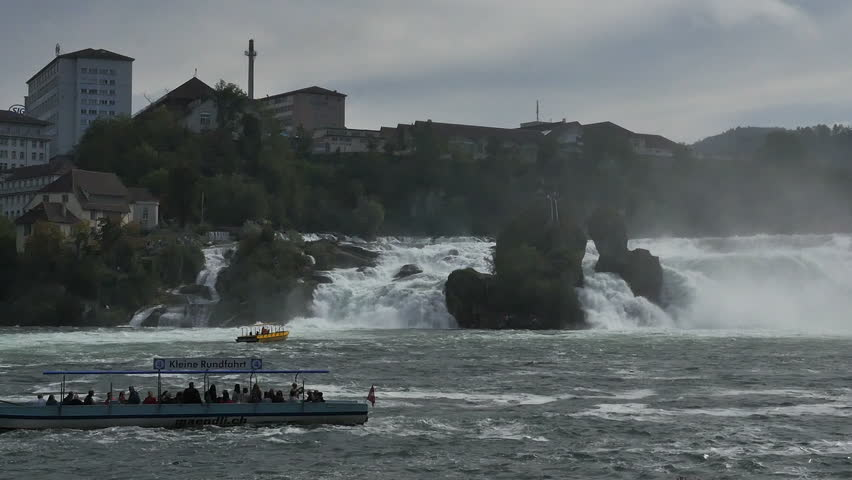RHINE FALLS, SWITZERLAND - SEPT 2014: Tourist excursion boats ply the waters below the famous Rhine Falls in Switzerland taking tourist into the mists below the falls. - HD stock video clip