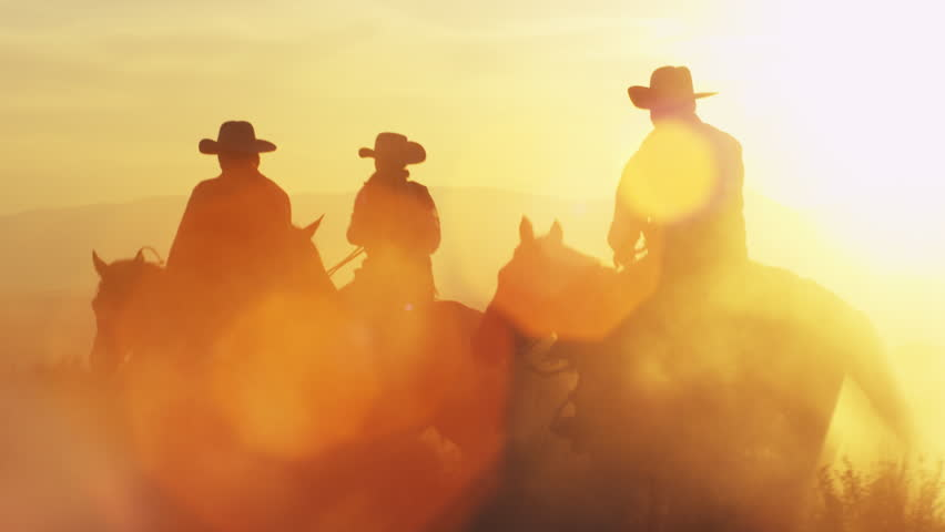 Cowboys galloping into dusk. Lens flare is visible.