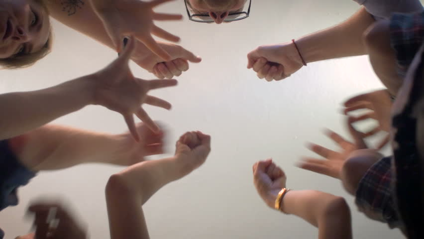 Low angle shot from below of a group of 5 young millennials place their hands together in the center of a circle and then cheer in a celebration of a successful event and shake hands and fist bump.