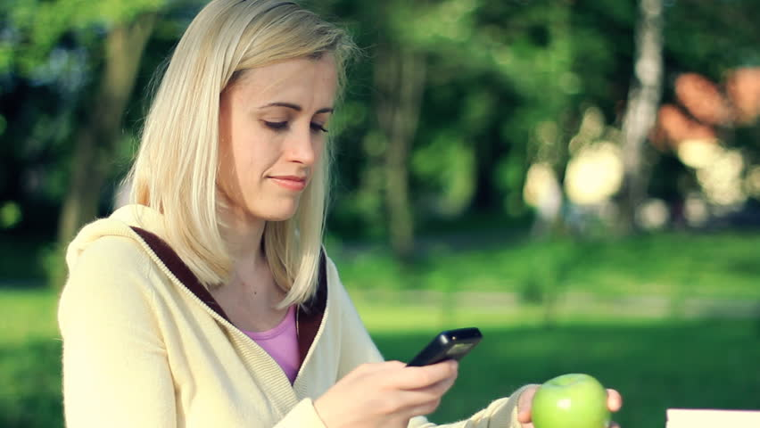 Attractive happy woman sending sms, texting in the park - HD stock footage clip