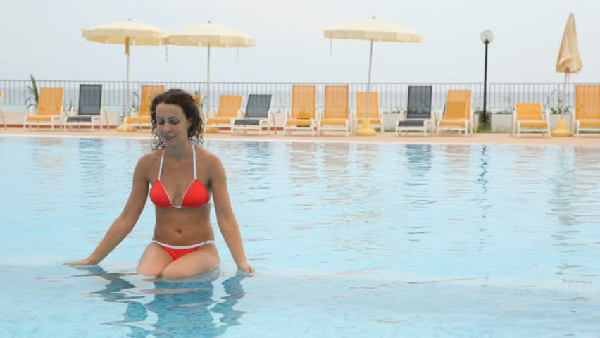 pretty young woman in red bikini sits in pool shallow water in front of chaise lounge and beach umbrella - HD stock footage clip