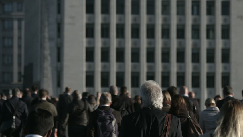 Large crowd of anonymous people in front of grey building in 4K. Large crowd of commuters and pedestrians walk across London Bridge to the City of London on a sunny morning. Framed for graphics.
