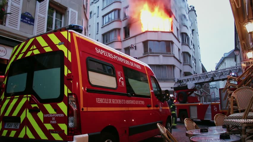 Firefighters arriving to control flames in an apartment in Paris. 4 OCTOBER 2015 - PARIS, FRANCE; An apartment explodes and catches fire, breaking all the windows and killing one person.