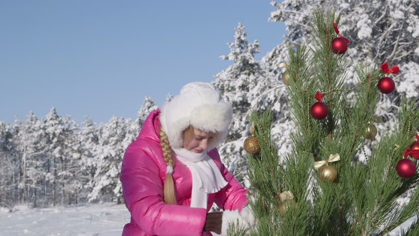 Child decorating Christmas tree in snow covered winter forest - HD stock video clip