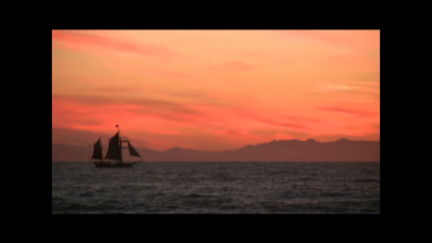 A tall ship sailboat sailing across the sea at sunset.