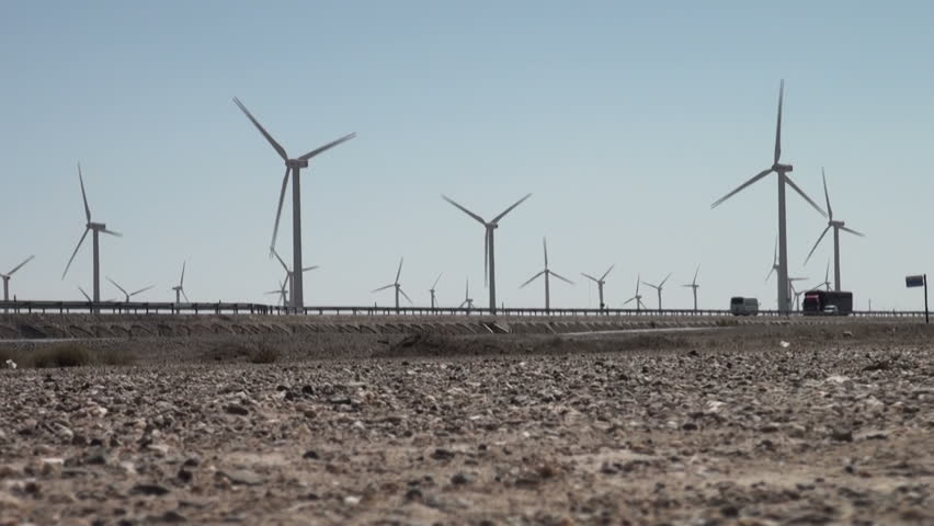 Windmill park along a highway in the Chinese desert. - HD stock footage clip