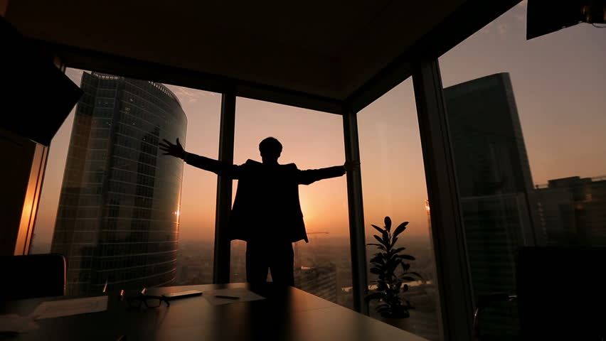 Businessman looking out the window in a contemplative way, Dolly shot, sunset, silhouette