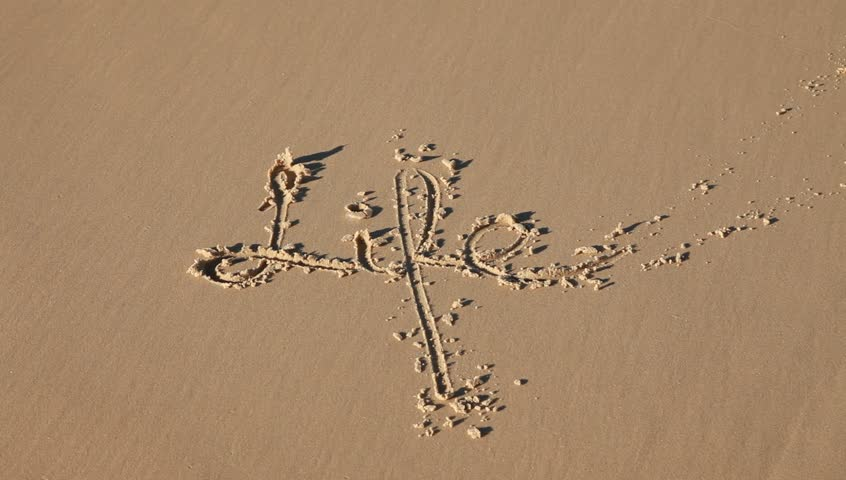 the word life written in the sand gets washed away by a wave - HD stock video clip