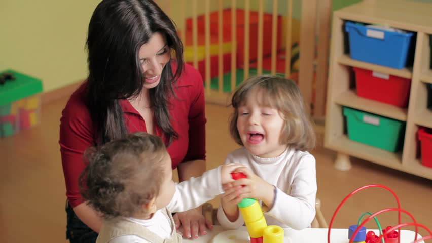 Kindergarten with teacher, toddler and 2-3 year girl playing with blocks toy