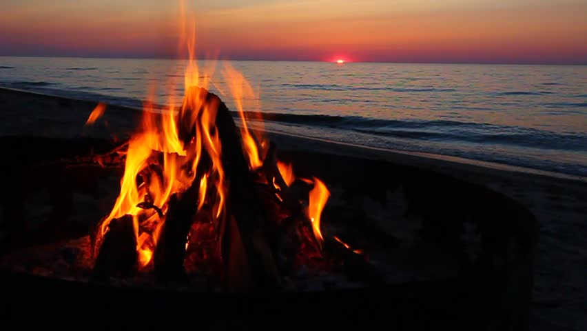 Campfire burns brightly at sunset along the beautiful beach of Lake Superior in northern Michigan - HD stock video clip