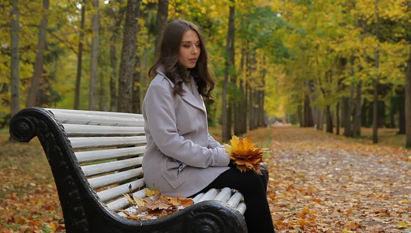 Portrait of a pretty woman with maple golden leaves sitting on a bench in a beautiful autumn park waiting for someone.