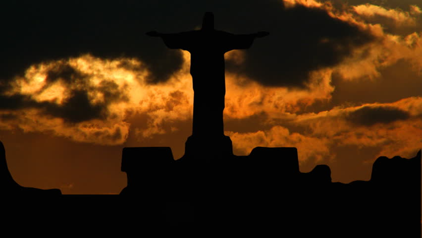 Statue of Christ on Sugar-loaf, in Rio de Janeiro, Brasil, with orange sunset in the background. - HD stock video clip