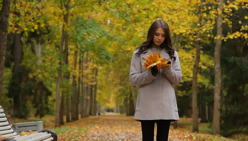 Pretty woman with maple golden leaves in a beautiful autumn park. She is walking, sitting on a bench, waiting for someone. - HD stock footage clip