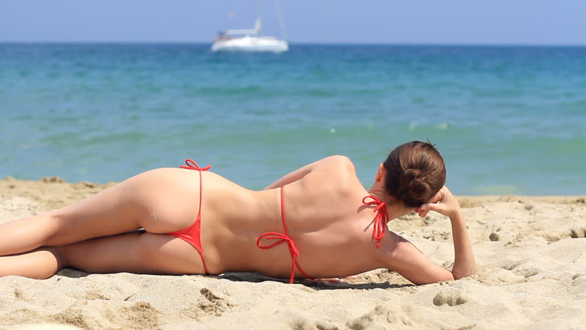 Sexy girl in red thong bikini lying on the beach - HD stock video clip