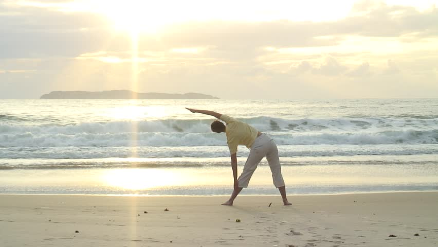 HD 1080i: Young woman doing yoga on the beach at sunrise in Bombinhas - Brazil. Tripod.