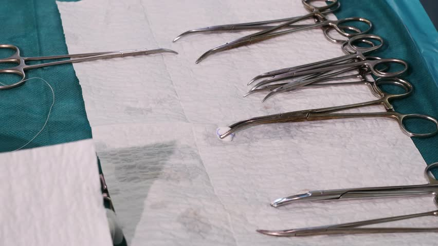 Nurse's hand picking up surgical instruments from a tray during an operation, Dolly shot, Close-up, 4k footage - 4K stock video clip