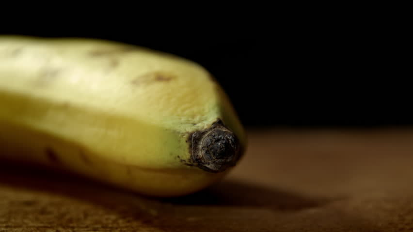 Banana close up background HD stock footage. A Banana in close up isolated against a black backdrop with negative space for text overlays. - HD stock video clip