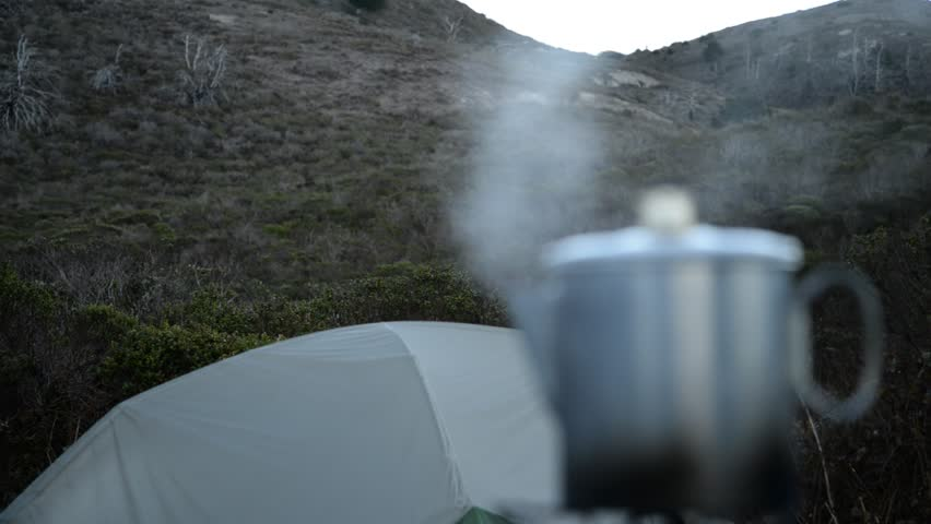 coffee percolating at the ocean-side campsite, with rack focus - HD stock footage clip