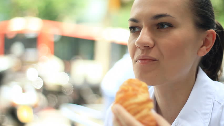 Attractive woman eating croissant in restaurant, outdoors, camera stabilizer shot - HD stock video clip