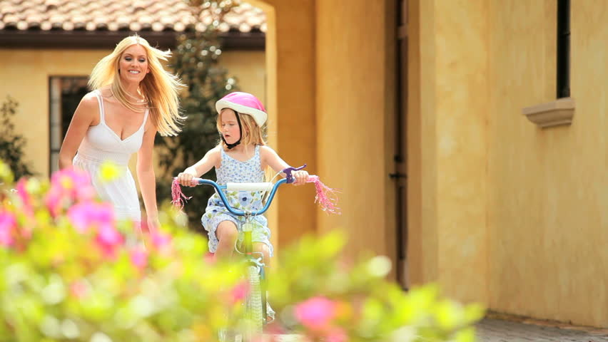 Blonde mother teaching her young daughter to ride a bicycle - HD stock footage clip