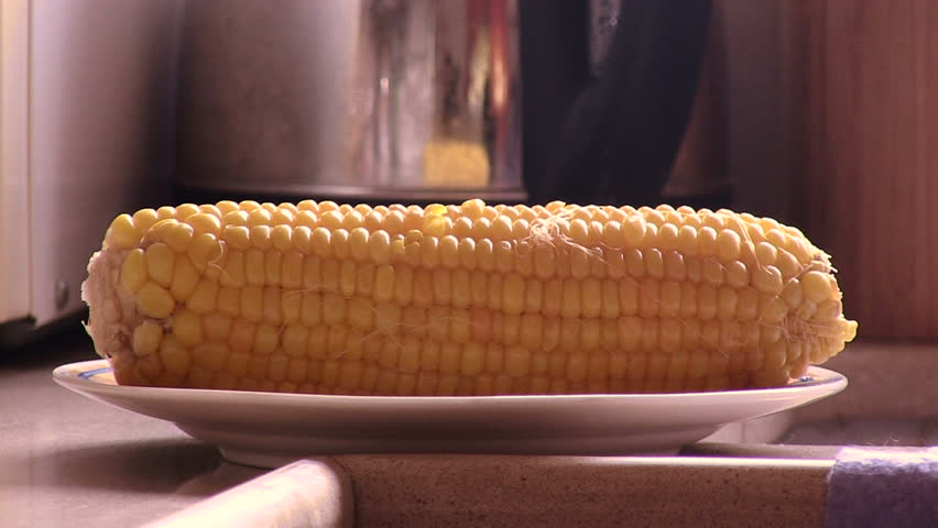 Hot sweet corn on the plate and steam emanating from it.